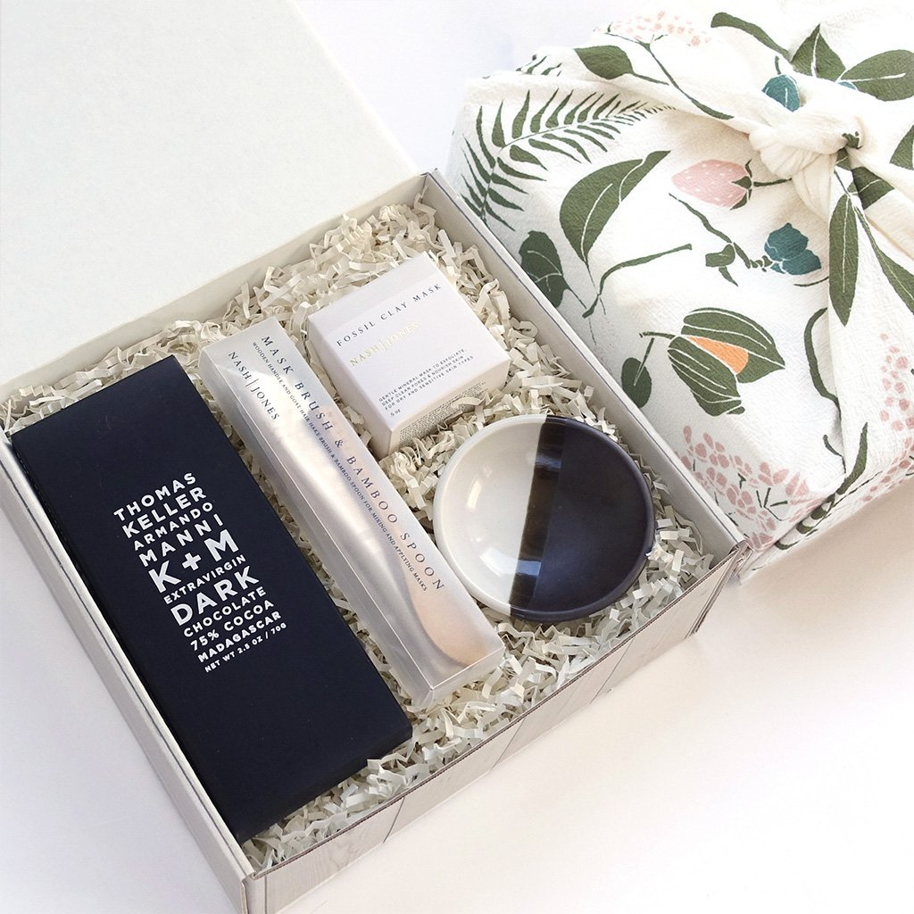 KADOO Mother's Day Radiant Beauty gift box with tea towel wrap. Contains dark chocolate bar, clay mask set with mixing bowl, wooden spoon and a soft goat hair brush.