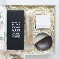 KADOO Radiant Beauty gift box. Contains dark chocolate bar, clay mask set with mixing bowl, wooden spoon and a soft goat hair brush. Wrapped in flour sack tea towel in floral pattern.