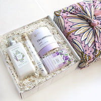 KADOO Mother's Day Lavender Lullaby Spa gift box with furoshiki tea towel wrap. Contains hand lotion, bath balm, bar soap, and tube of bath salt.