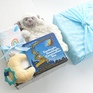 KADOO baby boy gift box wrapped in Furoshiki star pattern in cotton. Contains Mary Meyer lamb lovey and moon silicone rattle, Cotton Muslin Swaddle, and New York Times bestselling Goodnight, Goodnight Construction Board Book.