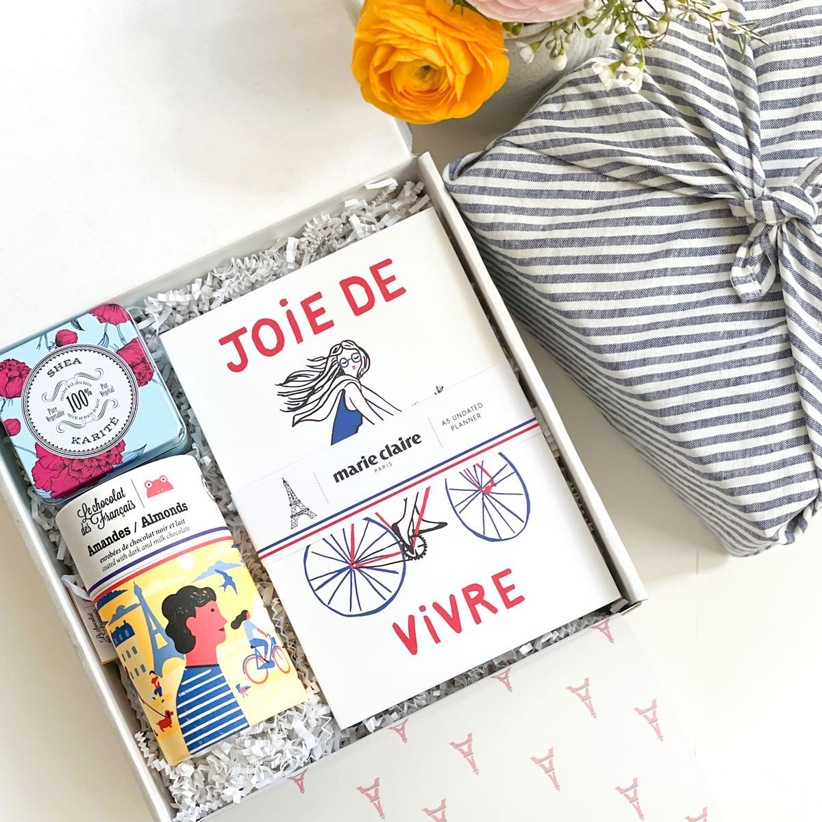 KADOO Joie De Vivre – Parisian theme gift box. Wrapped in Furoshiki stripes French linen. Contains: Marie Claire Paris journal, dark and milk chocolate almond, and shea travel soap.