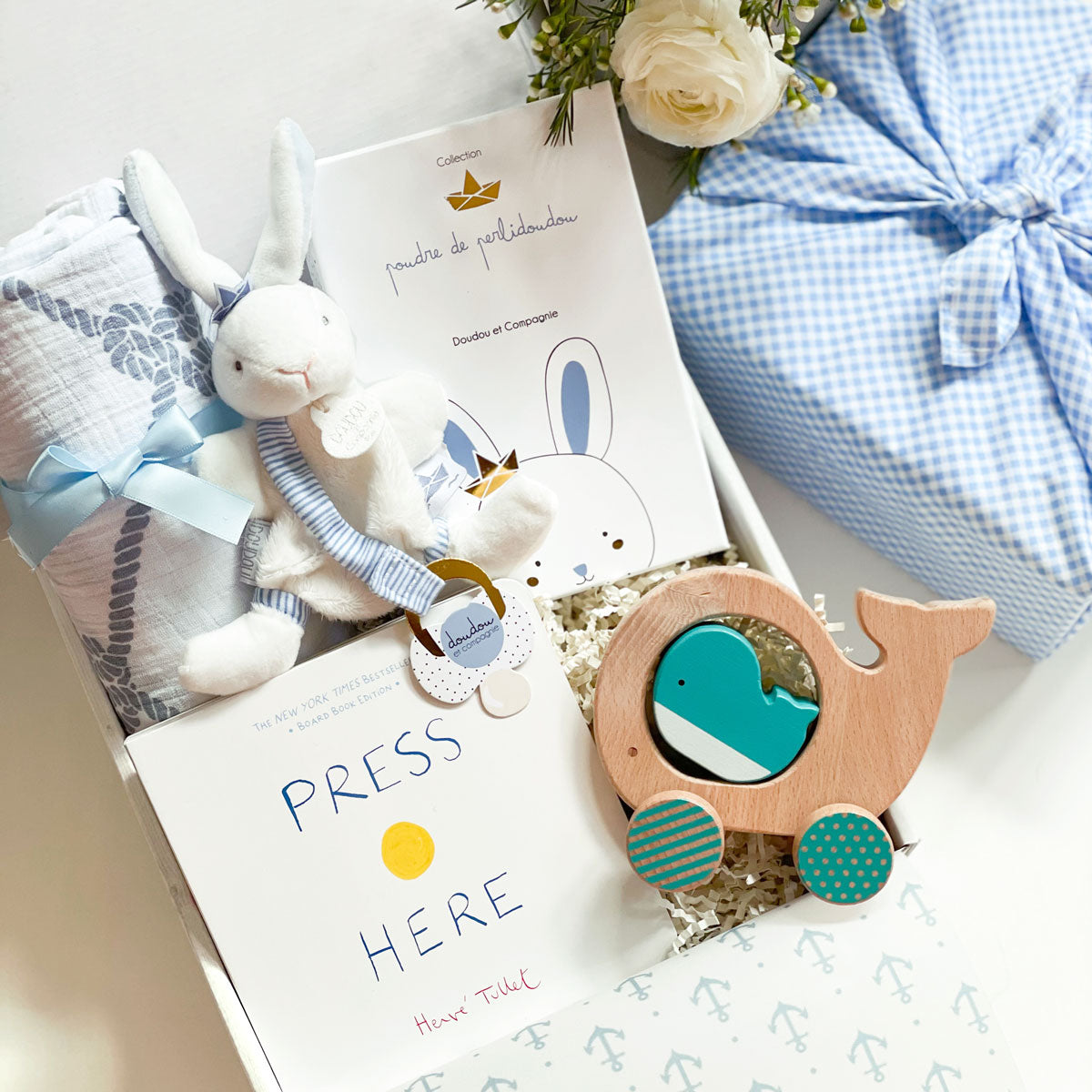 kadoo baby boy gift box in Furoshiki blue checkers. Inside: bunny plush, press here board book, wooden whale & swaddle.
