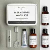 Dapper Man Gift Box product feature of: Men's Society Weekender Wash Kit box with shampoo, cleansing face wash, face cream, tooth brush and paste laid on paper.