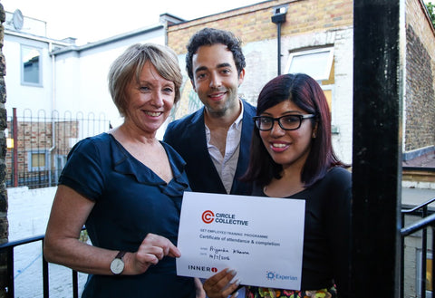 Circle Collective graduate stands with her certificate and two of Circle's corporate partners