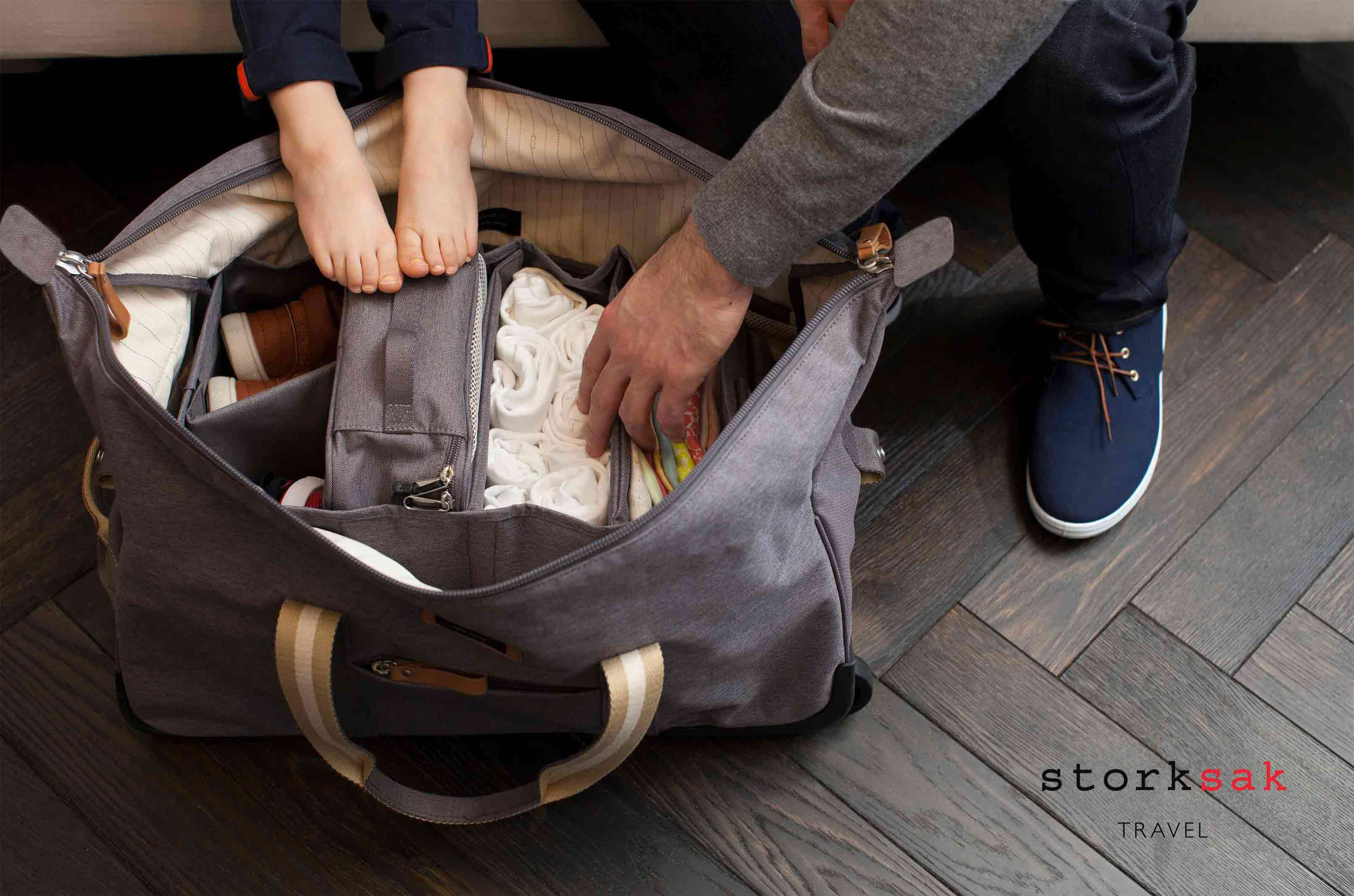Storksak Travel Cabin Carry-on Grey hospital bag open on floor with child and model | Maternity hospital bag | baby accessories |Storksak - Award-winning Baby Changing Bags & Accessories