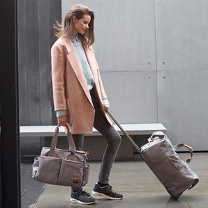Model holding Storksak Travel Cabin Carry-on Grey hospital bag | Maternity hospital bag | Storksak - Award-winning Baby Changing Bags & Accessories