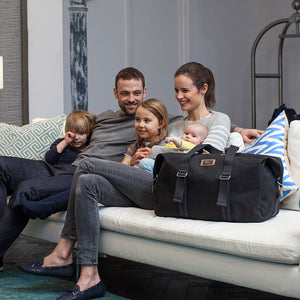 Storksak Travel Duffle Black hospital bag on sofa with family | Maternity hospital bag | Storksak - Award-winning Baby Changing Bags & Accessories