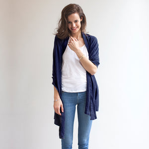 model wearing Mothers Cocoon Navy Breastfeeding Shawl as shrug | Multi-use nursing shawl | Storksak – Award-winning Baby Changing Bags & Accessories