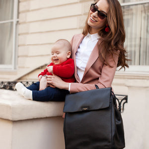 St James leather black | storksak changing bag | black leather handbag | mum holding baby and carrying baby bag