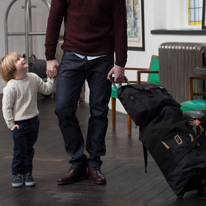 Model holding Storksak Travel Backpack Black changing Bag on Cabin Carry-on | Backpack changing bag | Storksak - Award-winning Baby Changing Bags & Accessories