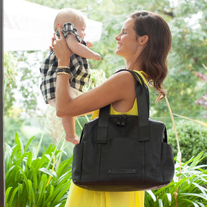 model wearing kym leather black Baby Changing Bag | shoulder bag Changing Bag | Storksak – Award-winning Baby Changing Bags & Accessories