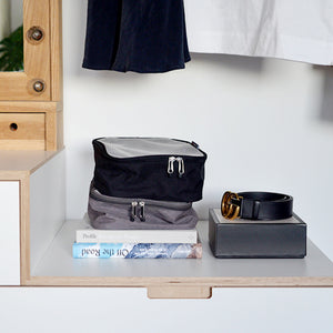 Packing Blocks Grey and Black Baby accessories stacked in wardrobe | Storksak Travel Baby accessories | Storksak - Award-winning Baby Changing Bags & Accessories