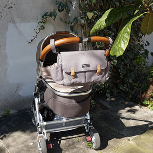 Storksak Travel Stroller Organiser Grey baby accessories on buggy outside | Travel baby accessories | Storksak - Award-winning Baby Changing Bags & Accessories