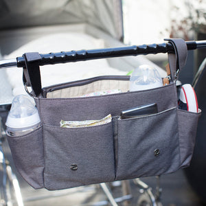 Storksak Travel Stroller Organiser Grey baby accessories open on buggy outside | Travel baby accessories | Storksak - Award-winning Baby Changing Bags & Accessories