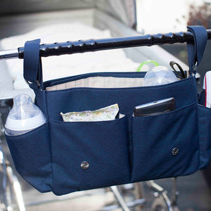 Storksak Travel Stroller Organiser Navy baby accessories open on buggy outside | Travel baby accessories | Storksak - Award-winning Baby Changing Bags & Accessories