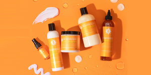 Flat lay of natural hair products with orange background. Nancy's Kitchen products caters to the health and styling needs of naturally kinky, coily and curly hair textures.