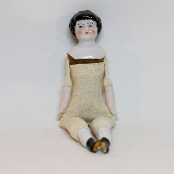 "Antique CHINA SHOULDER DOLL HEAD DOLL 7 ¾"" long; shoulder head measures 2"" tall by 1 ⅝"" wide at shoulders. Blue eyes, rosy cheeks, closed mouth and molded black curly hair with straight cut bangs. Bisque arms and legs, hand-sewn clean muslim body; stuffing appears original. No fractures. Likely German circa 1900."
