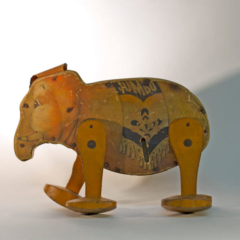 GO 'N' BACK JUMBO was one of the first Fisher Price toys. The paper lithograph decorated wooden wind-up orange elephant with circus blanket, orange oilcloth ears, and four wooden legs was offered in 1932 by Frank Tea & Spice Company of Cincinnati, Ohio as an advertising toy for its JUMBO brand peanut butter. Rare Find!