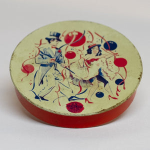 This round TIN-LITHOGRAPH RATCHET-STYLE NEW YEARS EVE NOISEMAKER made by US Metal Toys from the late 1940s to 1950s depicts a couple, a man dressed in a top hat and tailcoat and a woman in cha-cha costume dancing. The light-colored background is filled with red and blue balloons and ribbon streamers.