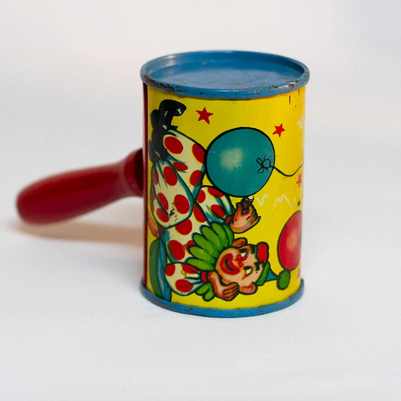 "This is an older style tin LITHOGRAPH CLOWN NOISEMAKER that likely dates to the 1930s or 1940s is in the shape of a small can. The lithograph depicts two clowns, one dressed in a white and red polka-dot clown suit and the other is ""toothless"" and dressed in blue plaid. Scene background in yellow. A red wooden handle is"