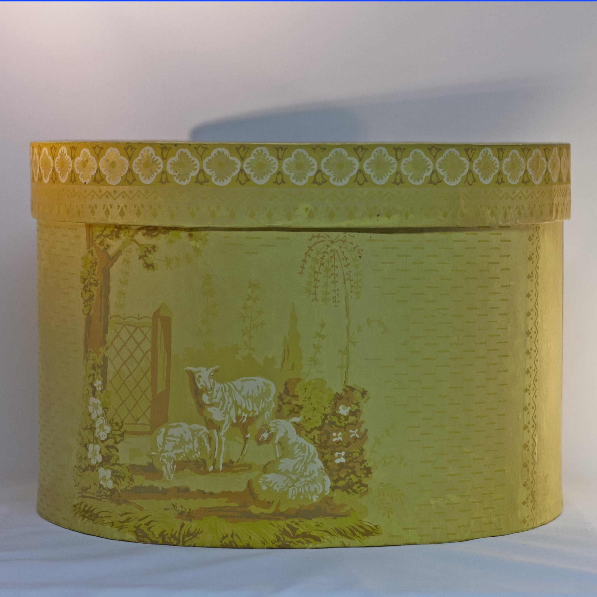 "Reproduction of a ""BRIDE'S BOX"" made from slightly oval shaped large hat box covered in vintage yellow wallpaper featuring lambs and a Colonial girl. Inside and bottom papered with pages from the Maine Antique Digest, September 1977. Measures about 10"" high by 15"" in length by 13"" wide."