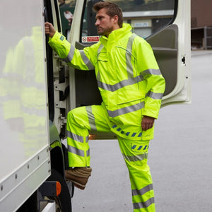 A man wearing PULSAR yellow hi-vis clothing getting into the cab of a lorry
