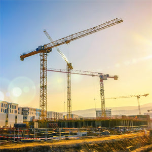 a construction site with multiple cranes on a sunny day