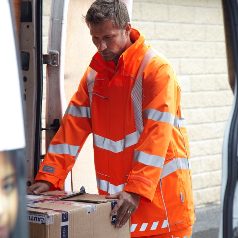 Man wearing PULSAR® high visibility orange coat holding a box