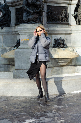 Loraly in Classic Sheers, a black skirt and a winter coat, wearing black sunglasses and looking very cool