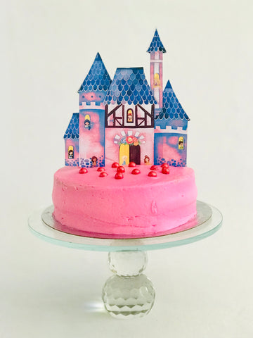 Cake topper of a princess castle on a pink cake