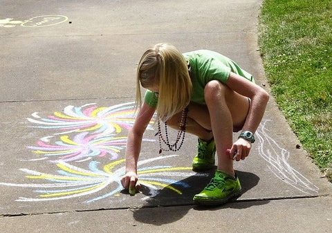 Child drawing sidewalk chalk