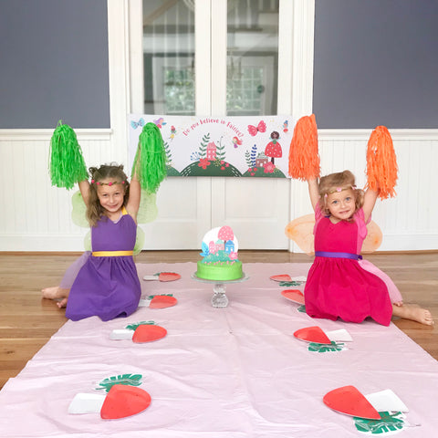 Two girls dressed as fairies at a fairy birthday party with toadstool plates