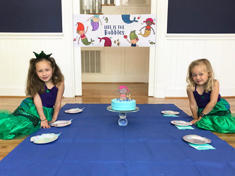 Shell paper plates with mermaid cake and kids dressed as mermaids