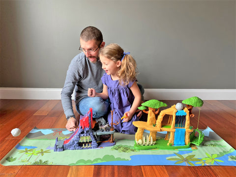 Dad playing with daughter with dinosaur toys