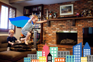 Imaginative play as a superhero, boy with cape jumping over buildings