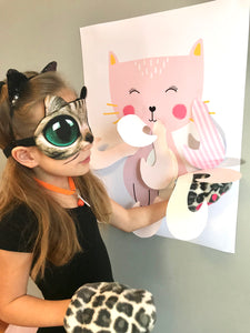 Child dressed as cat playing Pin the Tail on the cat
