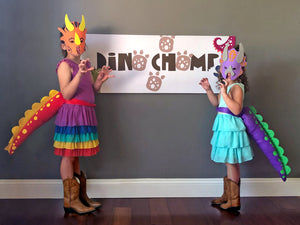 Dino chomp banner with kids dressed in dinosaur tails and masks