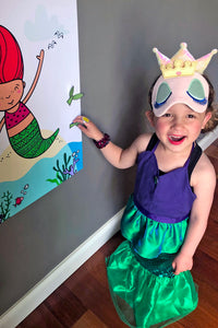 Child playing Pin the Fin on the Mermaid party game