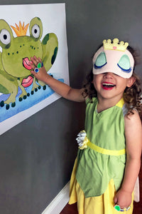 Child playing Pin the Kiss on the Frog at a princess party