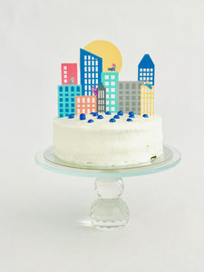 Superhero city skyline cake topper on white cake