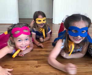 Girls in superhero costumes crawling on floor
