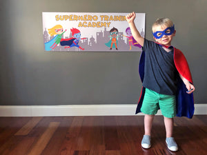 Boy dressed as a superhero in front of a superhero banner