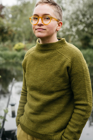 A white person with short hair and orange glasses stands outdoors. Trees can be seen in the background. The person is wearing an olive green, raglan, garter stitch sweater with a turtle neck