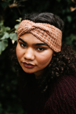 A black woman with long curly hair wearing a dark burgundy jacket looks up at the camera. She is wearing a light brown knitted hair band/ear warmer with a twist at the top.