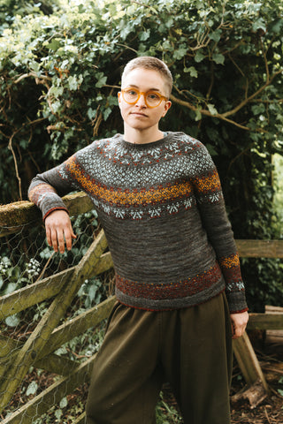A white person with short grey/brown hair leans on a wooden gate in front of a dark green hedge. They are wearing olive green baggy trousers and a colourwork sweater in dark grey with rust and grey colourwork in the yoke, along the bottom and at the ends of the sleeves.