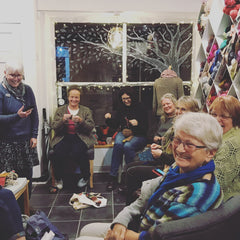 A group of women sit in All About The Yarn at night knitting and smiling