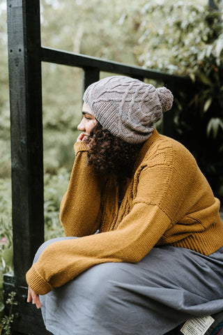 A black woman with long curly dark hair sits facing away from camera next to some railings. She is wearing a slouchy mid-grey, knitted hat, a mustard cardigan and a mid-grey skirt