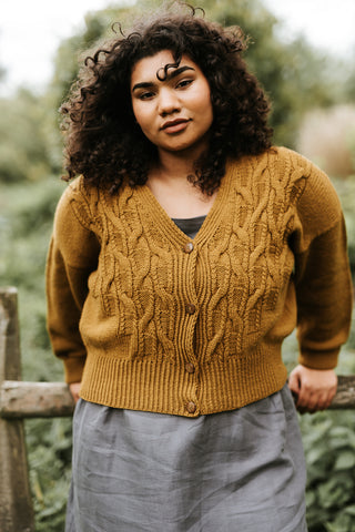 A black woman with long curly hair stands facing the camera leaning back on a low wooden fence. She is wearing a grey skirt and a mustard coloured knitted cardigan with a deep rib and cable and garter panels up the front.