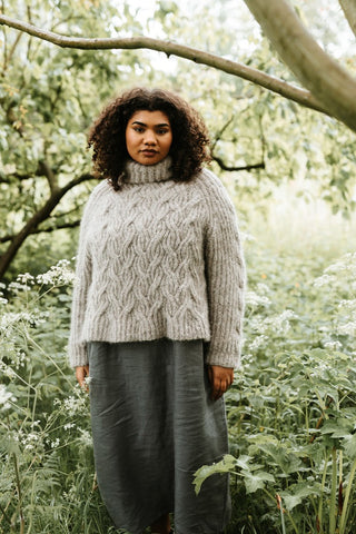 Soana: A black woman with long curly hair stands in undergrowth in a woods wearing a hand knitted jumper. It is a sumptous, roomy brioche roll neck jumper with a repetitive travelling stitch pattern all over the jumper