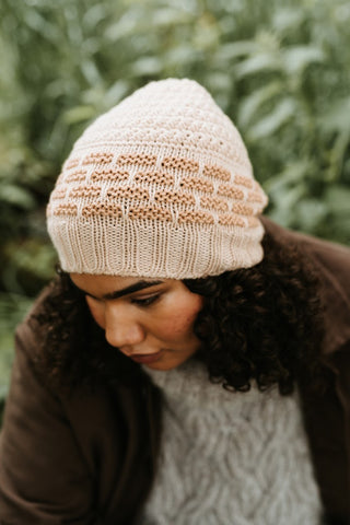 Seen from above, a black woman with long curly hair looks down. She is wearing a brown coat over a pale grey knitted jumper. She is wearing a knitted hat. The main body of the hat is cream with a textured stitch pattern on the top half and then fawn garter stitch blocks making a brick pattern against the cream on the bottom half.